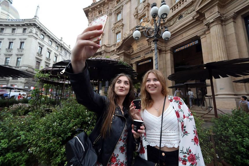 Two tourists pose for a selfie with their espresso cups outside the former post office building housing Italy's first Starbucks coffee shop.