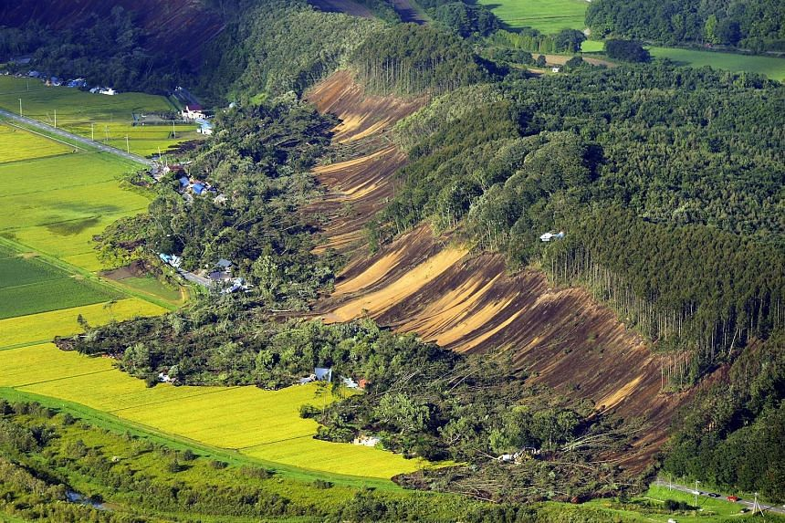 An aerial photo showing the aftermath of a large landslide in the rural town of Atsuma after the magnitude-6.7 earthquake hit Hokkaido in northern Japan early yesterday. About 32 people are still missing in Atsuma, where homes were flattened by a ser