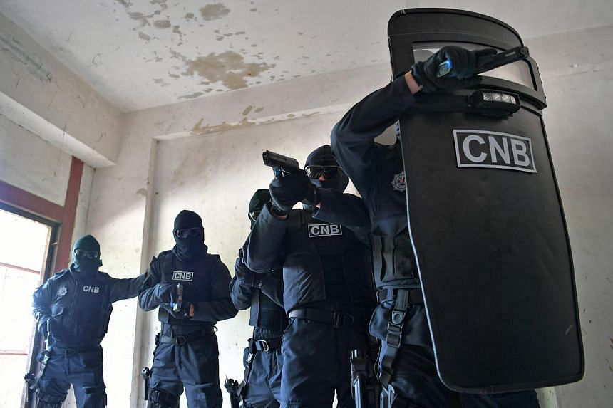 When dealing with armed gunmen, a Special Task Force point man carries a ballistic shield weighing 8kg and slowly leads the team into a flat.