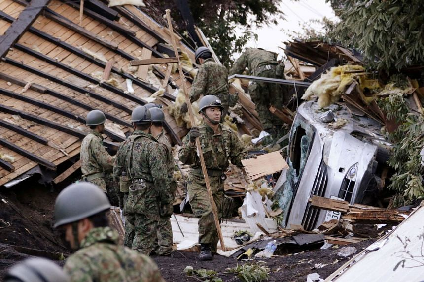 Members of the Japan Self-Defense Forces search for survivors from a house damaged by a landslide caused by an earthquake in Atsuma town, Hokkaido, on Sept 7, 2018.