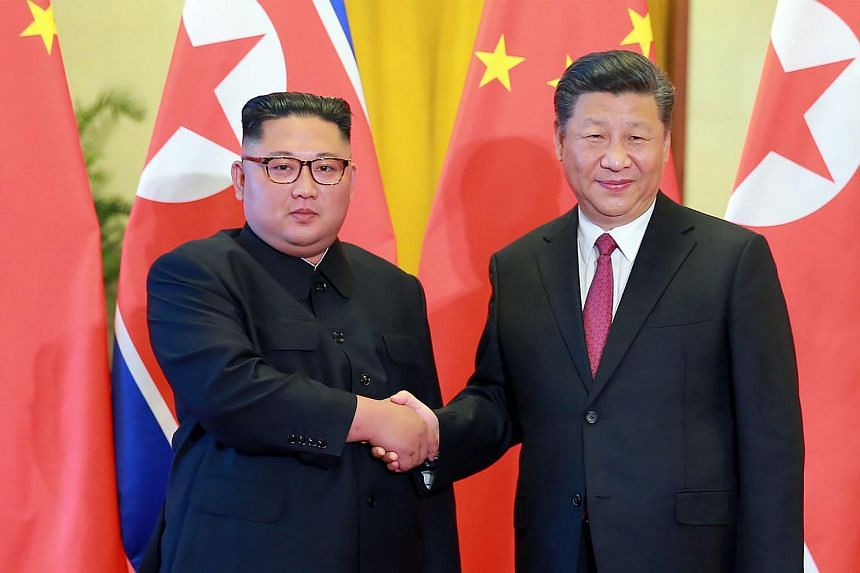 North Korean leader Kim Jong Un (left) shaking hands with Chinese President Xi Jinping at the Great Hall of the People in Beijing, on June 19, 2018.