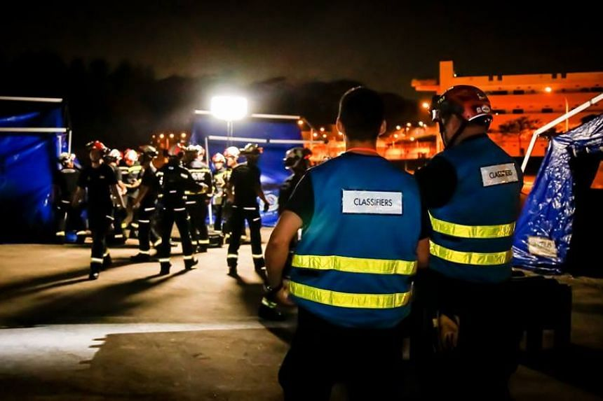 International classifiers from the United Nations' International Search and Rescue Advisory Group observing the Singapore Civil Defence Force's Operation Lionheart Contingent at work during a 36-hour disaster search-and-rescue simulation exercise tha
