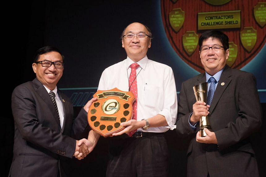 LTA chairman Alan Chan presenting the Contractors Challenge Shield to Shanghai Tunnel Engineering Co (Singapore)'s workplace safety and health manager Thant Zaw (left) and project director Khor Eng Leong.