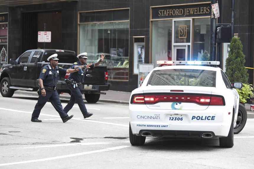 Police officers run to stop a driver following a shooting nearby in Cincinnati, Ohio.