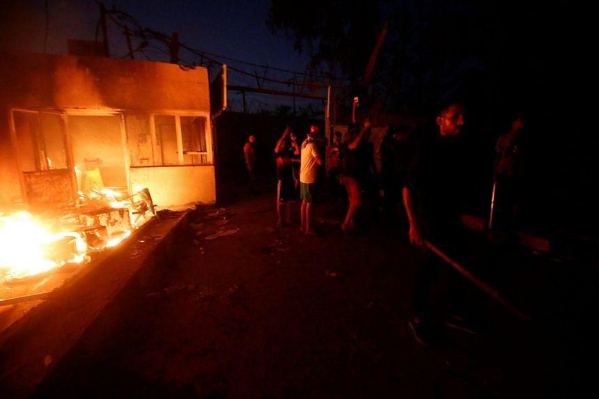 Iraqi protesters are seen near the burnt Iranian Consulate in Basra, Iraq.