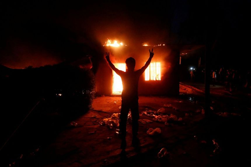 Iraqi protesters are seen in front of the burnt Iranian Consulate in Basra, Sept 7, 2018.