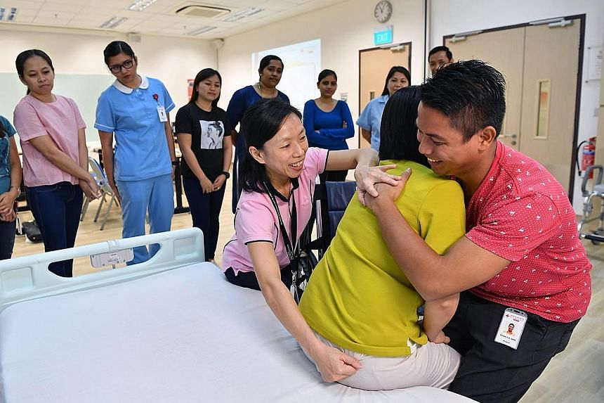 Principal physiotherapist Margaret Goh guiding a trainee on shifting a person from bed to wheelchair at the Community Training Institute.