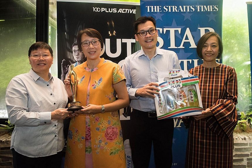The Straits Times' sports editor Lee Yulin (left) and Jennifer See (right), general manager of F&N Foods, presenting the ST Star of the Month August award to Yuen Shuang Ching and Walter Lien, who were present on behalf of daughter Constance, the Asi