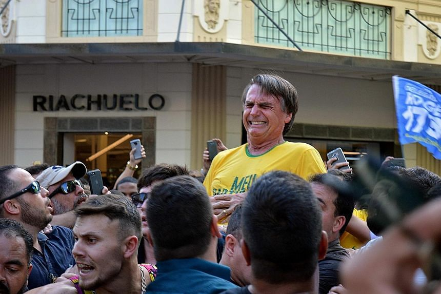 Mr Jair Bolsonaro (above) reacting after being stabbed in the abdomen during a rally in Juiz de Fora, Brazil, on Thursday. In a screen grab (left), the knife can be seen.