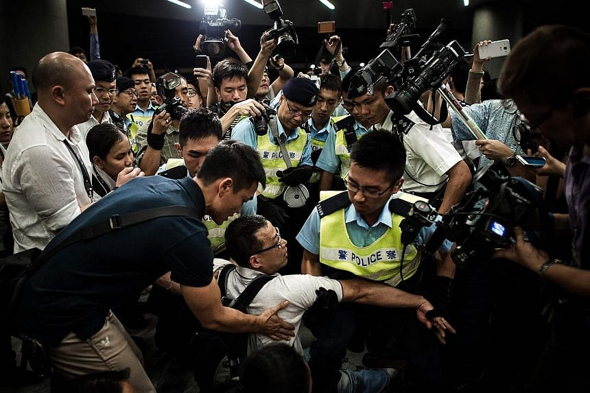 Police removing protesters from the Legislative Council grounds in a file photo taken on June 14, 2014. Hong Kong's Court of Final Appeal yesterday freed the 13 pro-democracy activists who stormed the place.