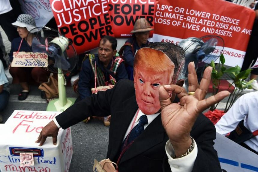 An environmental activist wearing a face-mask depicting US President Donald Trump takes part in a demonstration in front of the United Nations building, in Bangkok, on Sept 8, 2018.