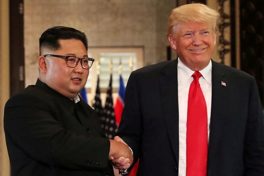 US President Donald Trump and North Korea's leader Kim Jong Un shake hands after signing documents during a summit at the Capella Hotel on Sentosa, Singapore, on June 12, 2018.
