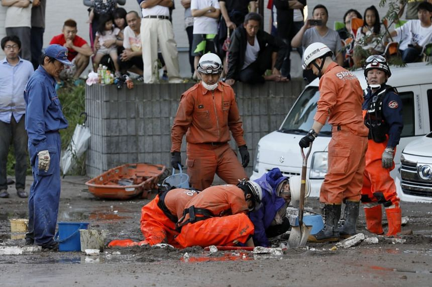 Rescue workers helping a woman trapped in mud following a powerful earthquake in Sapporo, Hokkaido, northern Japan, on Sept 6, 2018.