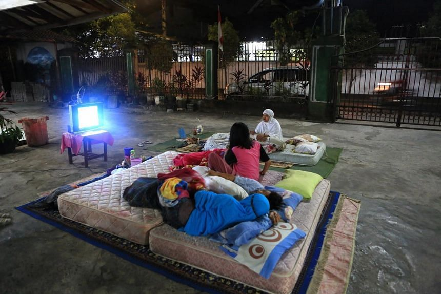 Survivors sleeping outside their house in Mataram, West Nusa Tanggara, on Aug 10, 2018. The Health Ministry has deployed a medical team to assist West Lombok in handling malaria cases.