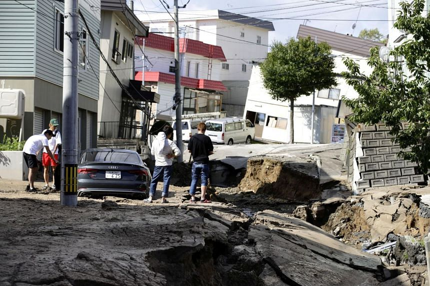 People looking at an area damaged by an earthquake in Sapporo, Hokkaido, on Sept 6, 2018.