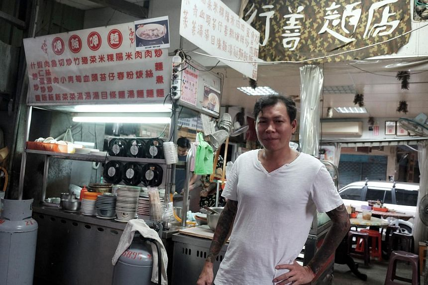 Yen Wei-shun, a former criminal, posing for a photo in front of his noodle shop in Panchiao district, New Taipei City.