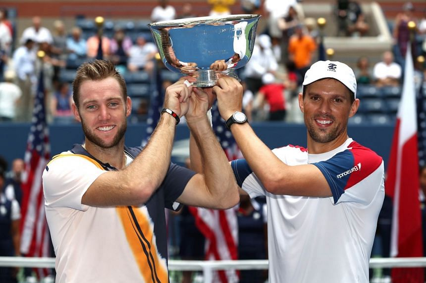 Jack Sock and Mike Bryan of the US celebrate victory with the winners trophy.