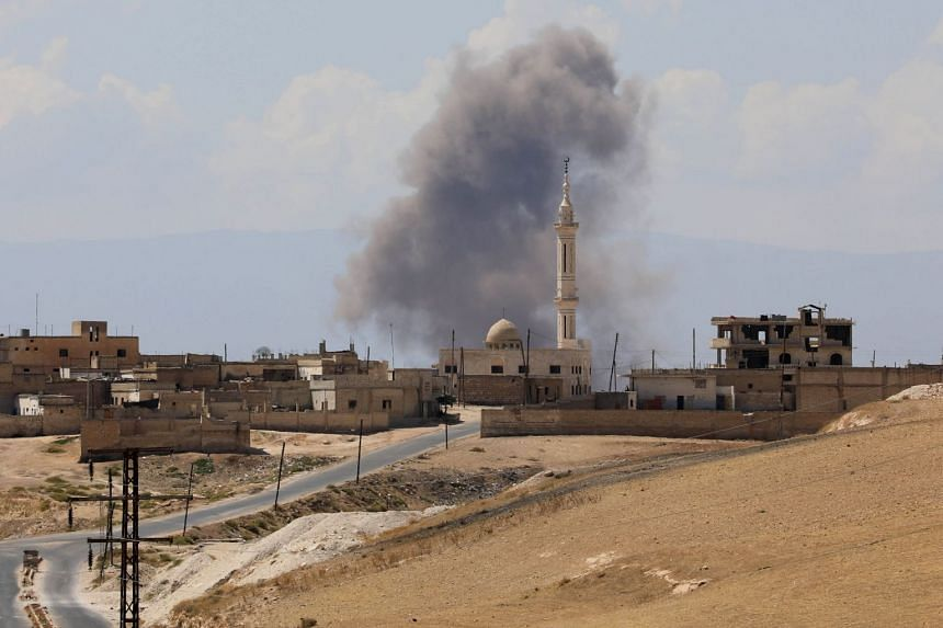 Smoke billows following Syrian government forces' bombardment around the town of Khan Sheikhun on the southern edges of rebel-held Idlib province.