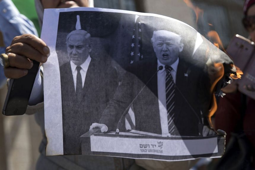Palestinians burning a picture of Trump and Israeli Prime Minister Benjamin Netanyahu on Sept 4, 2018, following US aid cuts.