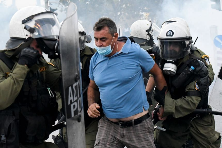 Policemen detain a protester at a demonstration against the agreement reached by Greece and Macedonia to resolve a dispute over the former Yugoslav republic's name.