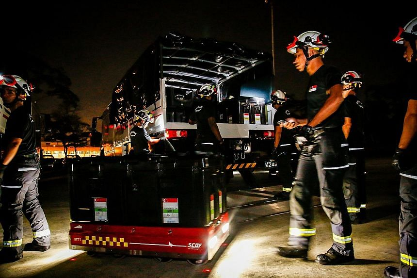 Above left: A Singapore Civil Defence Force officer from the Operation Lionheart contingent operating a semi-autonomous load-carrying transporter during the 36-hour exercise that began last Wednesday. Above right: Officers working to equip tents acco