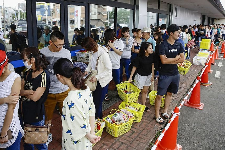 People lining up to buy foods outside a store after an earthquake hit the area in Sapporo, Hokkaido, northern Japan. In a display of renowned resilience, orderly queues formed outside convenience stores and supermarkets that remained open, with stoic