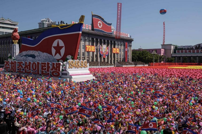 Participants wave flowers as they march past a balcony where North Korea's leader Kim Jong Un was watching the mass rally on Kim Il Sung square in Pyongyang, on Sept 9, 2018.