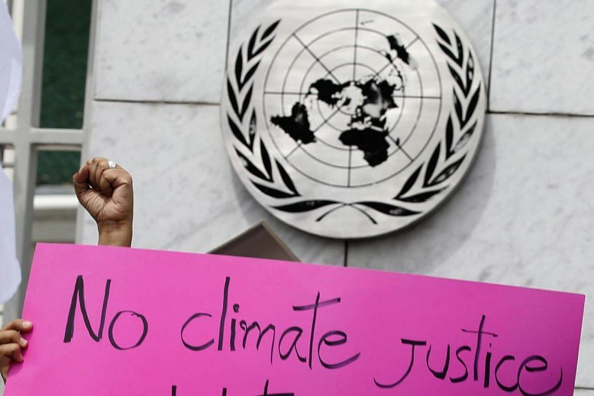 A climate change activist holds a placard during a demonstration outside the United Nations Centre during the first day of the UN Climate Change Negotiating sessions in Bangkok, on Sept 4, 2018.