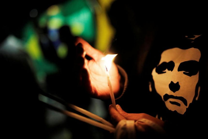 A supporter lights a candle for presidential candidate Jair Bolsonaro in front of the Albert Einstein hospital after he was stabbed in Juiz de Fora, in Sao Paulo, Brazil, on Sept 7, 2018.