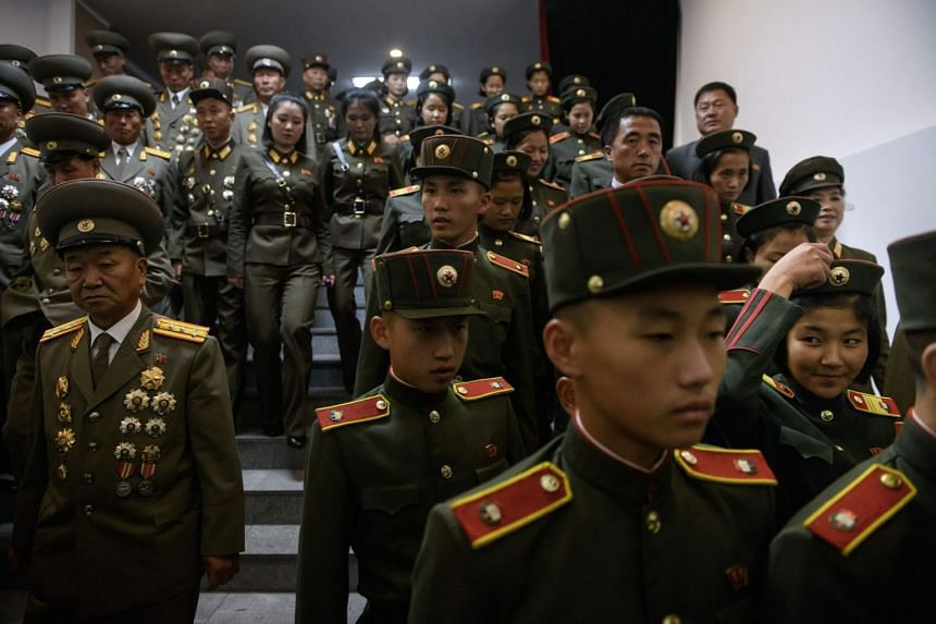 North Korean People's Army soldiers leave following a concert at the Pyongyang Indoor Stadium.