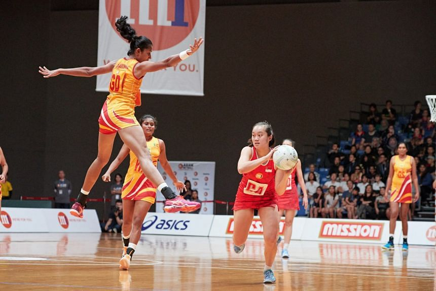 Singapore's Toh Kai Wei (right) attempts a pass with Sri Lanka's GD Chathurangi Jayasooriya jumping in to block.