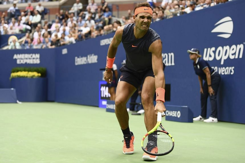 Rafael Nadal (above) grimaces as he lunges for a shot during his semi-final clash with Argentina's Juan Martin del Potro in the Arthur Ashe Stadium on Friday. The Spaniard retired after losing the first two sets as his right knee gave way, with del Potro
