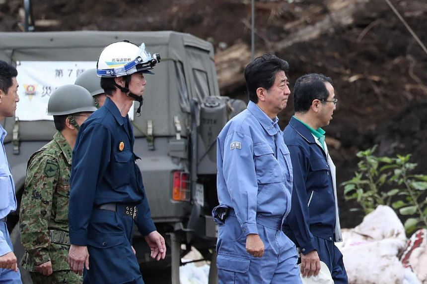 Japanese Prime Minister Shinzo Abe visiting the devastated city of Astuma on Sept 9, 2018 after a 6.6-magnitude earthquake hit the northern island of Hokkaido last Thursday.