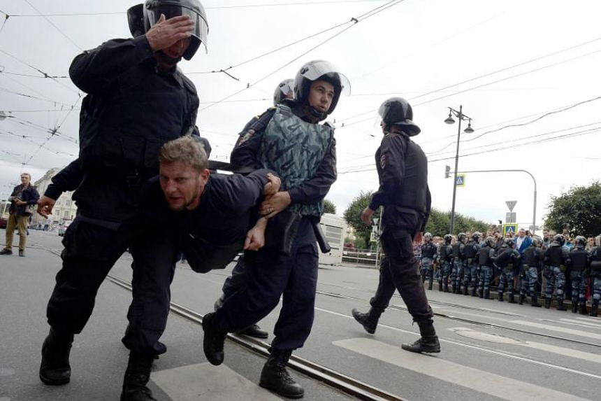 Police officers detaining a man during a protest rally against planned increases to the nationwide pension age in St Petersburg on Sept 9, 2018.