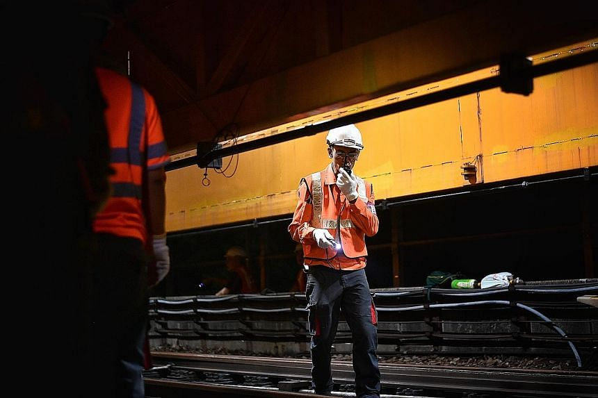 Members of the engineering team making the 300m walk from Boon Lay station to reach the maintenance work site. An engineering train used to transport the rails, along with other equipment and materials required for the replacement works, was on site.