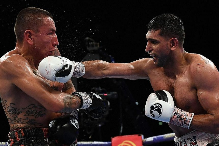 Britain's Amir Khan (right) using his famed hand speed against Colombia's Samuel Vargas in their welterweight bout on Saturday, en route to his 119-108, 119-109, 118-110 unanimous-decision victory.