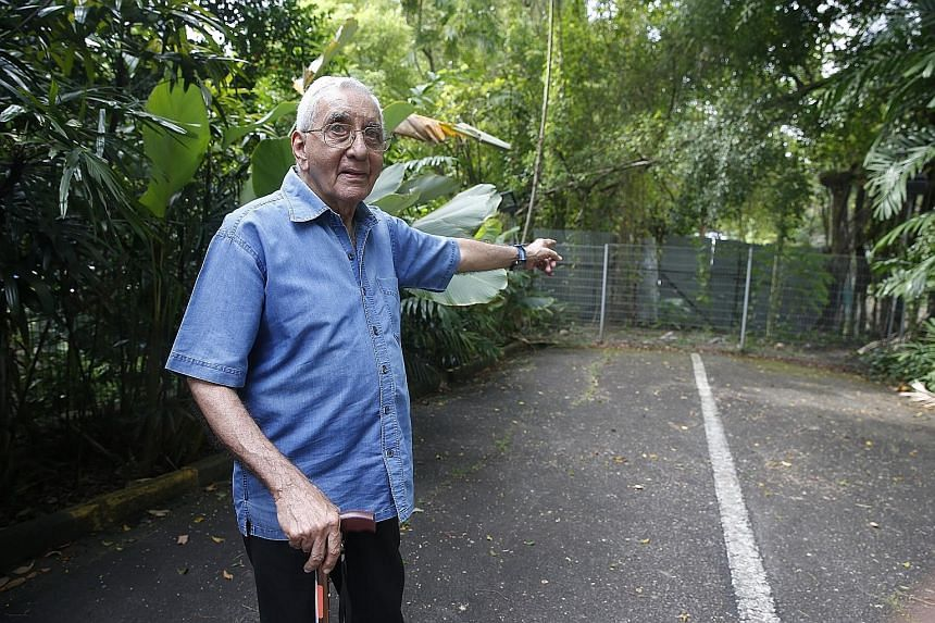 Grange Heights condominium management corporation strata title chairman Rustom Ghadiali pointing to the gate sealing off the disputed land. He told The Straits Times that legal bills had cost condo residents nearly $2 million. An aerial shot, taken f
