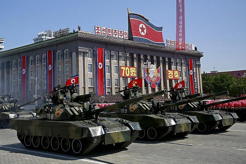 North Korean leader Kim Jong Un (right) acknowledging the crowd with Mr Li Zhanshu, a member of the Chinese Communist Party's Politburo Standing Committee, who was in Pyongyang as President Xi Jinping's envoy. Tanks and artillery were on display at t