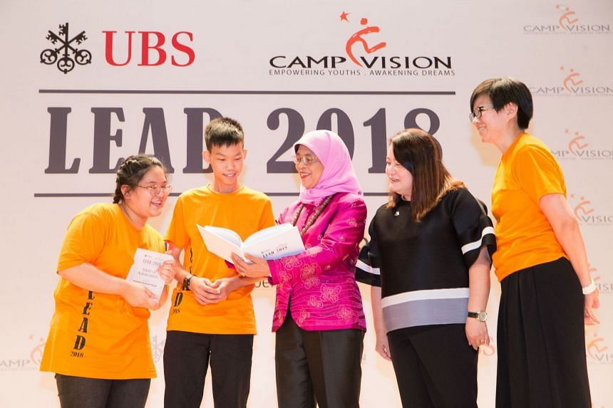 President Halimah Yacob being presented with a token of appreciation from students (from left) Dana Tan, Wesley Wee, Teo Lay Sie, Country Operating Officer of UBS Singapore, and Yeo Suan Wei, chairperson of CampVision Ltd.