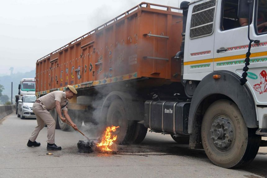 An Indian policeman removes a burning a tyre set alight along a national highway during a nationwide strike, in Guwahati, on Sept 10, 2018.