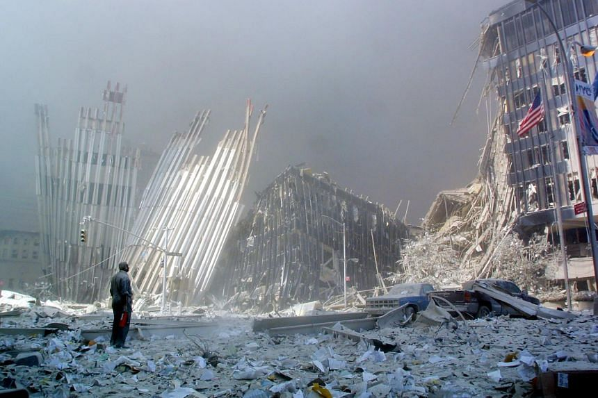 A man stands among rubble, calling out to ask if anyone needs help after the collapse of the first World Trade Center tower in New York, on Sept 11, 2001.