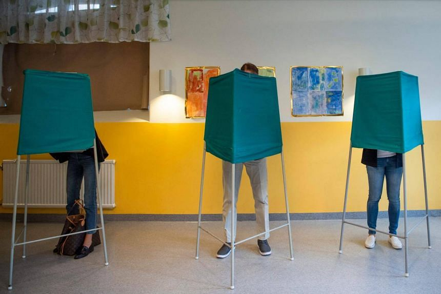 People at booths in a polling station during the Swedish general elections in Stockholm, on Sept 9, 2018.
