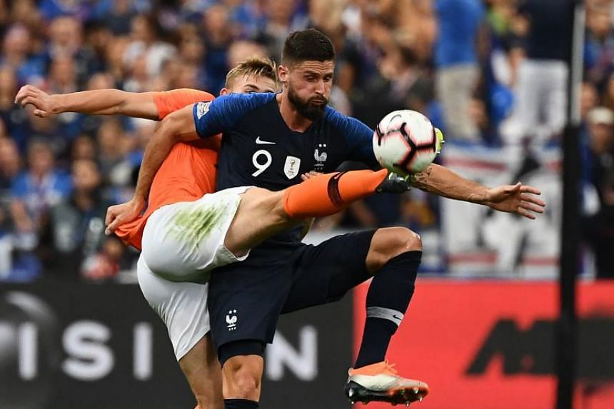 France's forward Olivier Giroud (right) vies for the ball during the UEFA Nations League football match at the Stade de France stadium, in Saint-Denis, northern of Paris, on Sept 9, 2018.