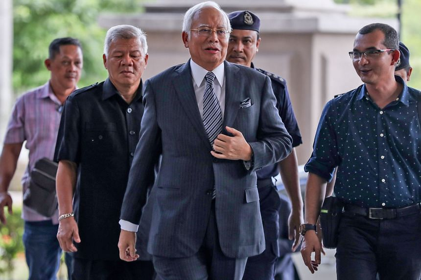 Former Malaysian premier Najib Razak being escorted by police officers at the Kuala Lumpur High Court last month. He posted a statement on his Facebook page yesterday regarding the RM116.7 million (S$39 million) seized in May from premises linked to