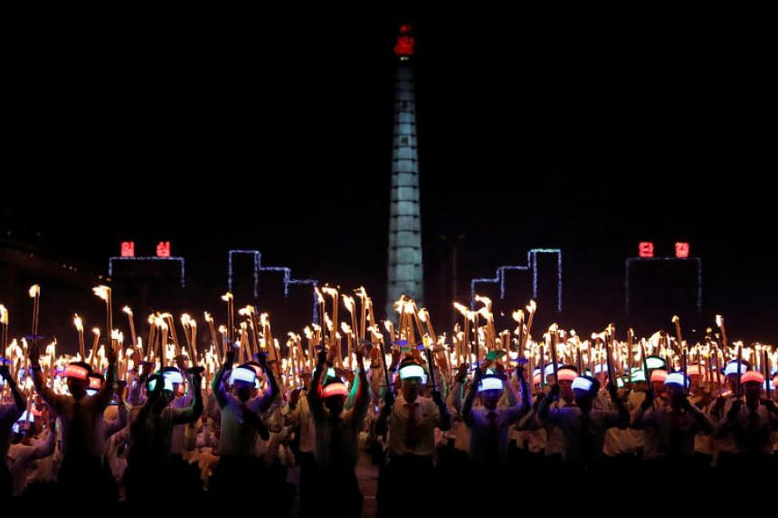 Participants shouting slogans as they carry torches during a torchlight procession to mark North Korea's 70th birthday.