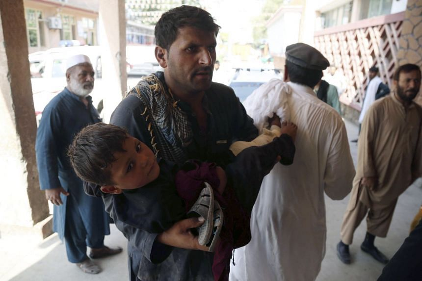 A young boy who was injured is rushed to a hospital to receive medical attention in Jalalabad.