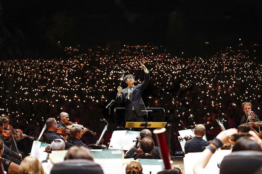 Mr Wong Kah Chun conducting the Nuremberg Symphony Orchestra during the Klassik Open Air concert that attracted 65,000 people. Instead of a baton, he is holding a sparkler like the audience as night falls over the park.