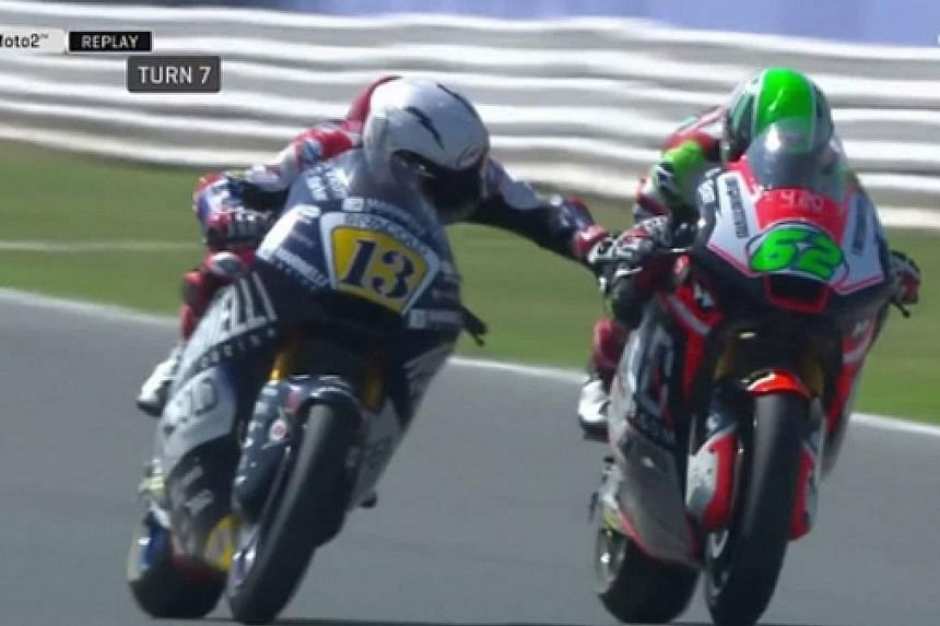 Romano Fenati reaching out to press Stefano Manzi's brake lever. The latter lost his balance briefly before regaining control of his bike.