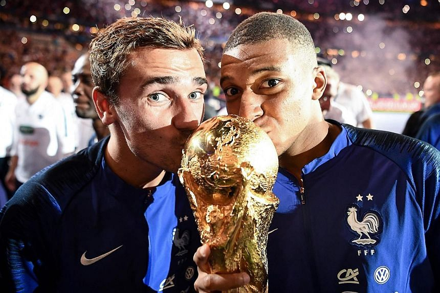 France forwards Antoine Griezmann (far left) and Kylian Mbappe just cannot get enough of the World Cup trophy as they celebrate with their countrymen at the Stade de France in Paris on Sunday.