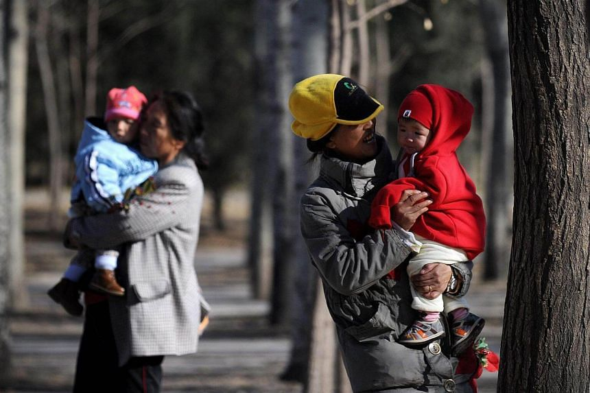 Chinese families at a park in Beijing. Three offices responsible for family planning have been removed from the new structure of China's National Health Commission.